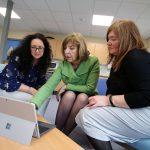 three women gathered around a Microsoft Surface