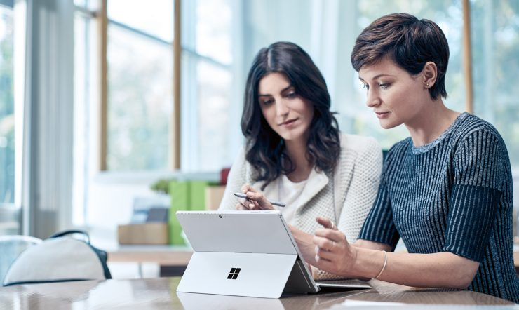 2 women working on a Microsoft Surface