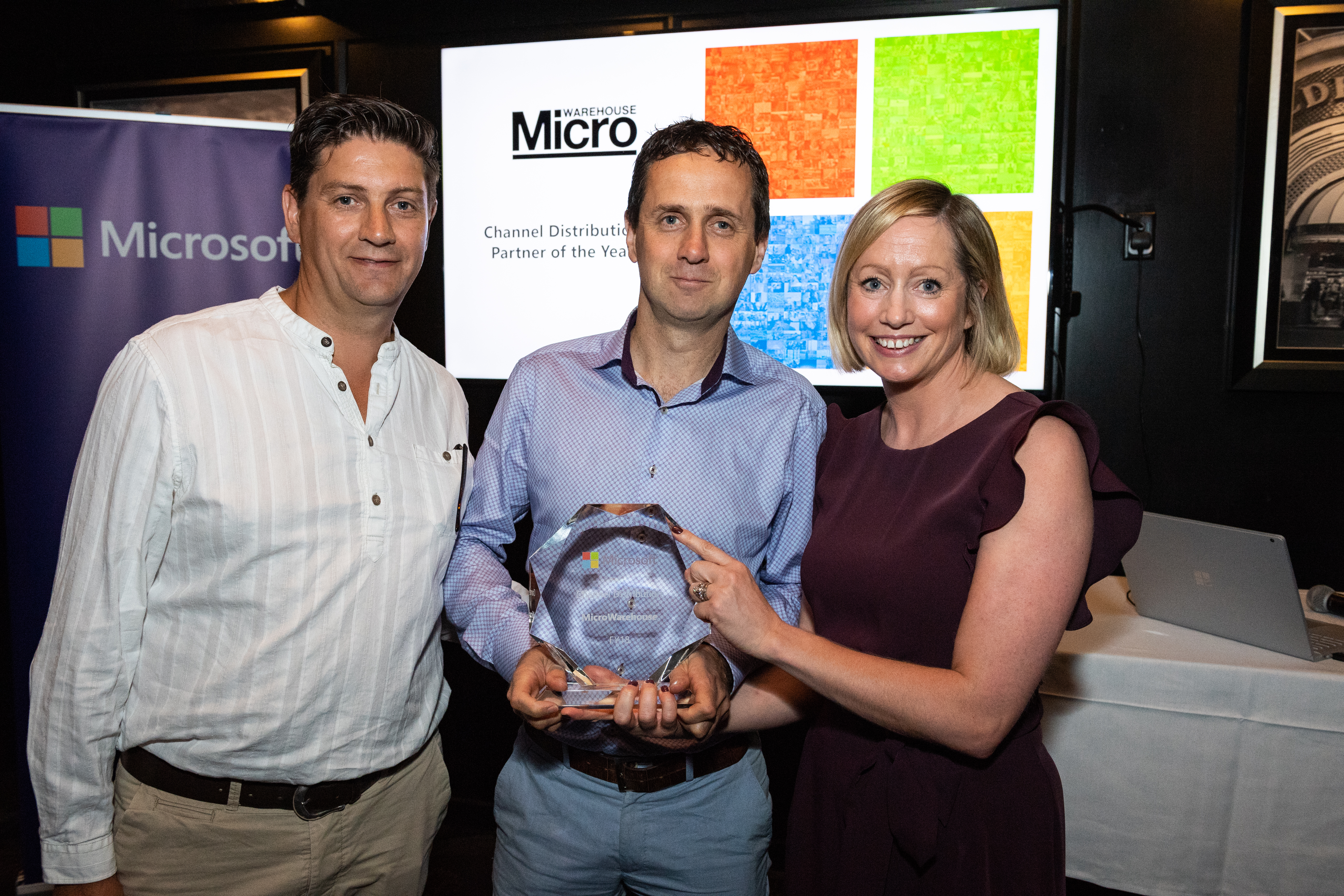Rory Wilson, Rob Driver from Microwarehouse receiving an award from Aisling Curtis