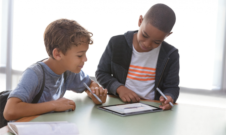 2 kids playing on a Surface Go