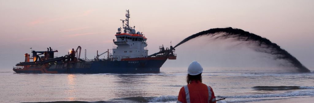 Employee of Van Oord looking at a Van Oord sand motor during sunset
