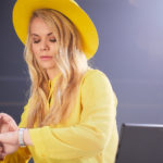 Woman with yellow hat and coat looking at her watch