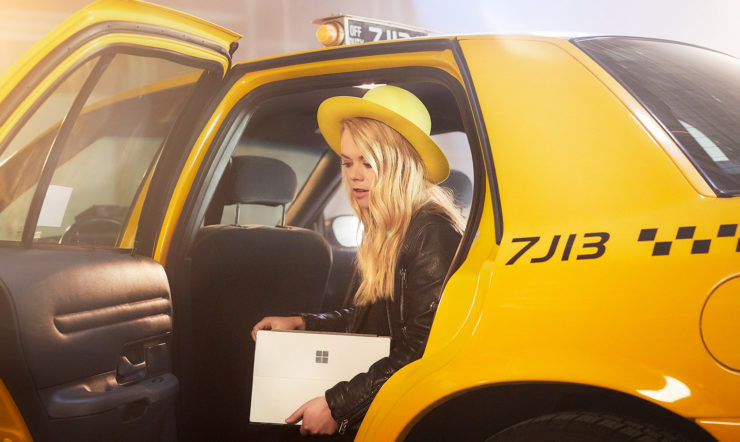 Woman with yellow hat stepping out of yellow cab with a Surface