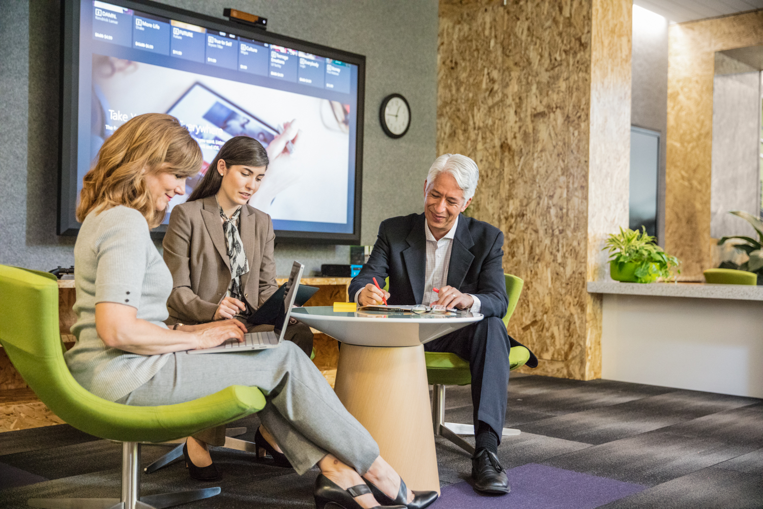 Group of two female and one male office workers brainstorming in informal office setting. Both women are using laptops while the man is writing. Large screen shown in background.