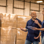 man and woman are standing in a warehouse