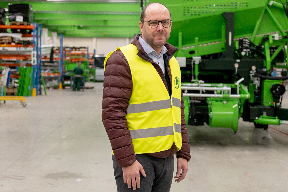 Koen Uyttenhove, IoT Manager at AVR, in a shed in front of a green agricultural machine.