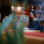 Image of a woman on her laptop in a coffee shop