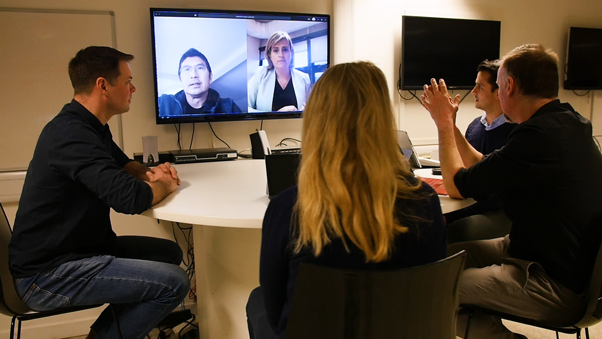 four people around the table video chatting to two people on Microsoft Teams