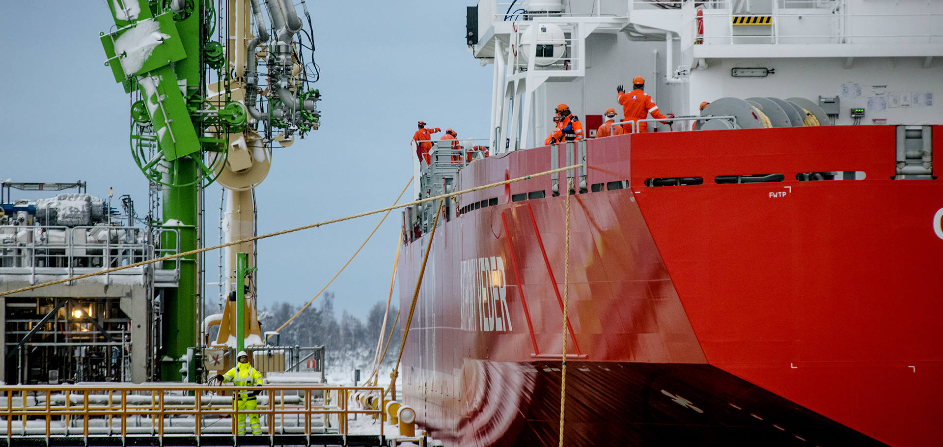 A large red ship with a few men onboard stationed at the shipyard