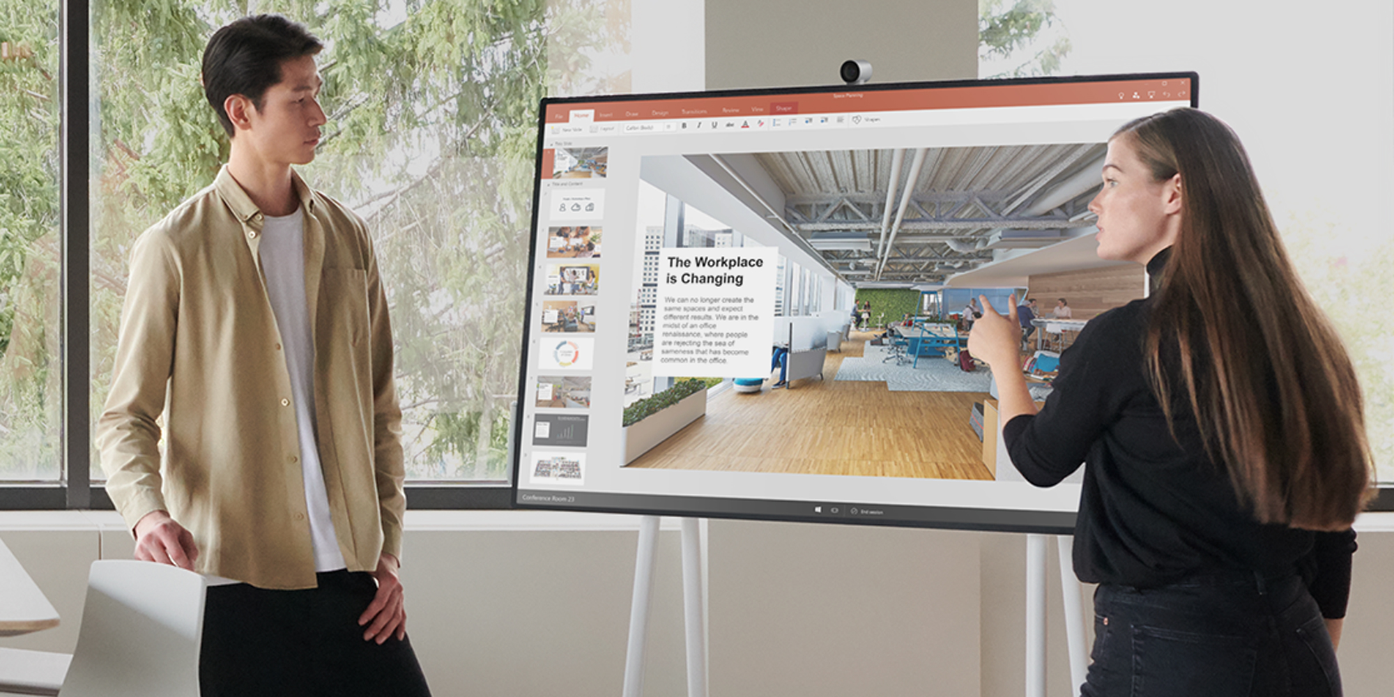 a man and a woman standing in front of a Surface Hub 2S