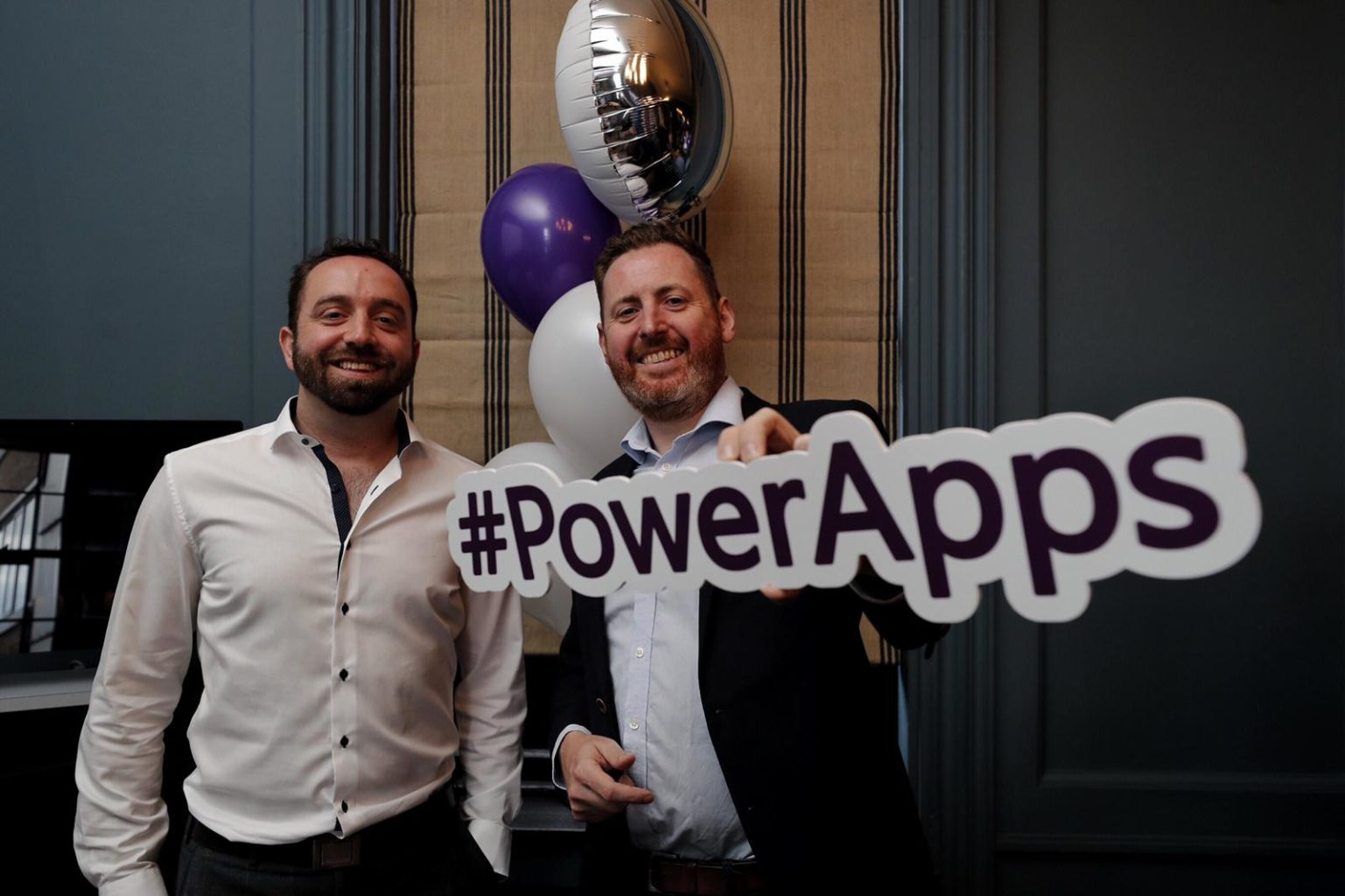 David Arnold & Paul Gilbride holding a PowerApps sign posing for the camera