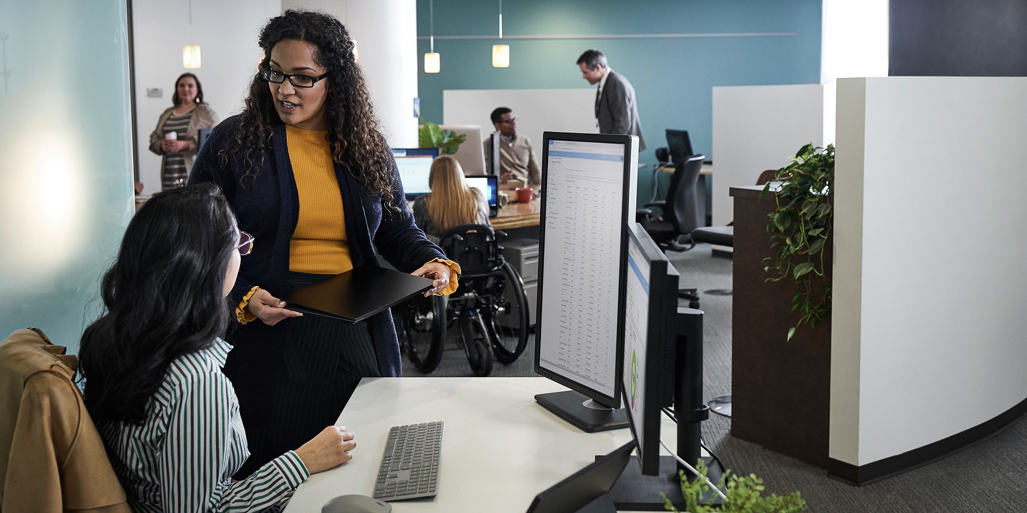 Two people sitting and standing in front of a computer