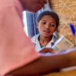A female child sitting and looking as a nurse writes in notebook in rural clinic of nutrition enhancement program in Madagascar.