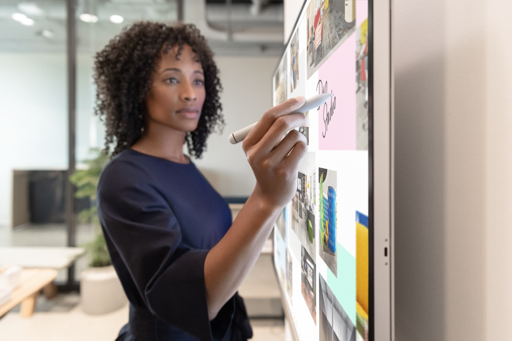 Woman executive working on Surface Hub 2S in Whiteboard with Surface Hub 2 Pen