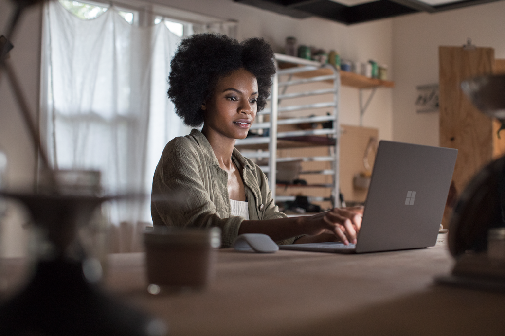 Female working on project using Microsoft Surface Laptop (platinum) in a ceramic workshop