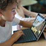 Children, students in classroom playing Minecraft on Surface Go. Contextual education.