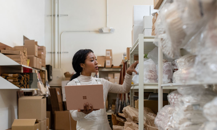 Contextual image of woman holding Surface Laptop 3 in Sandstone working in a warehouse.