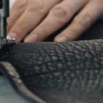 A close up of a hand sewing leather