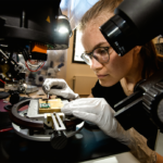 Female scientist wearing plastic gloves while examining a microchip in quantum technology lab.