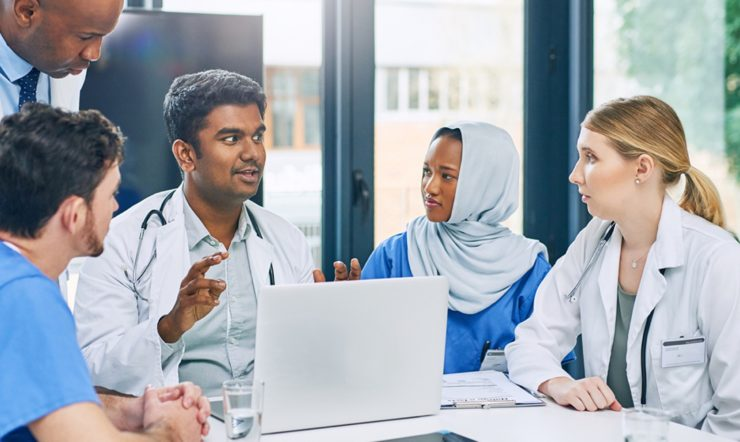 a group of medical professionals looking at a computer