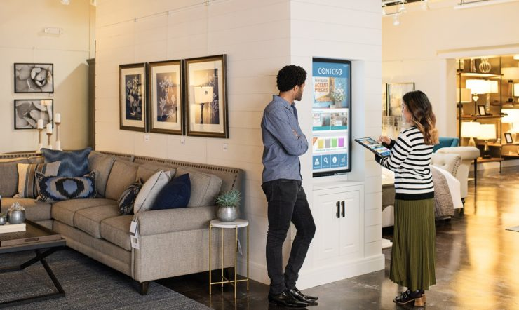 Female and male first line workers standing on sales floor in commercial retail store, in front of a wall-mounted monitor. She is using an Acer convertible laptop (folded open as a tablet) to navigate through images on monitor screen which shows product ads for home furnishings.