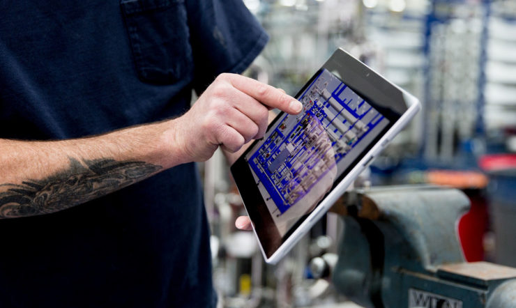 Man with a tattoo pointing at a tablet in a factory