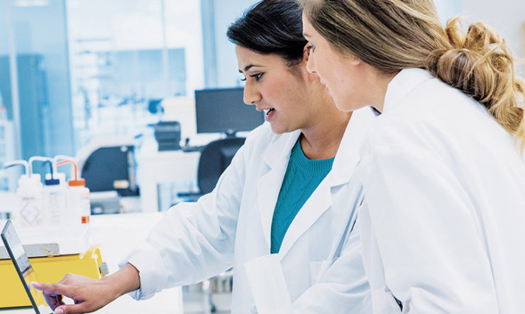 Two female healthcare professionals looking at a tablet