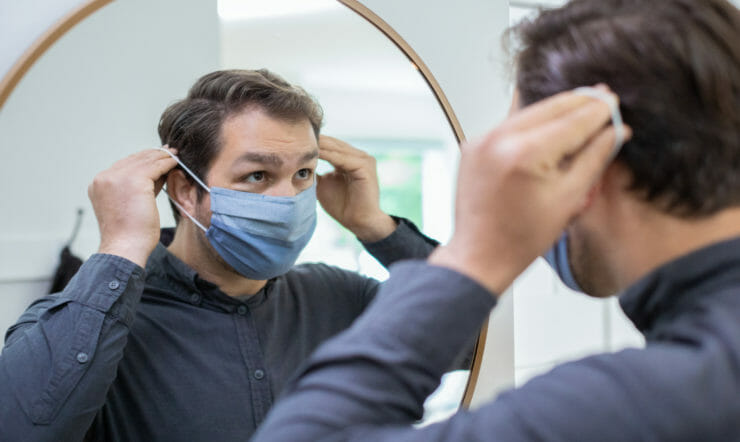 A male employee putting on a face mask while looking in the mirror.