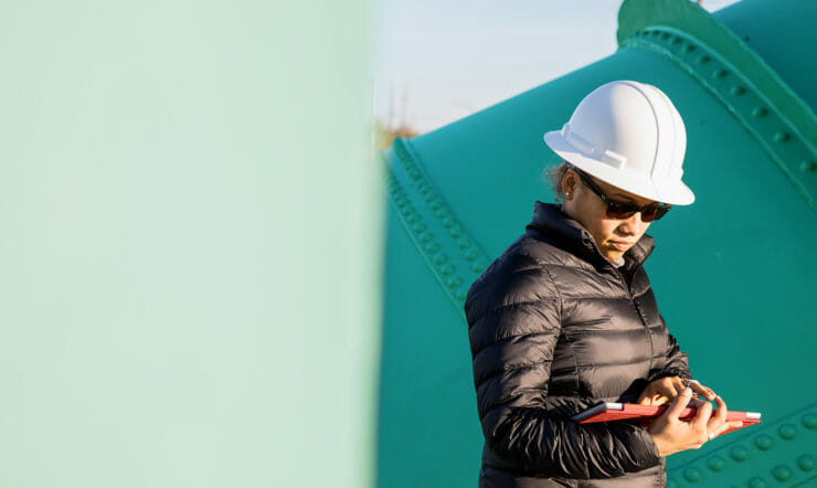 Adult woman in an industry holding a tablet