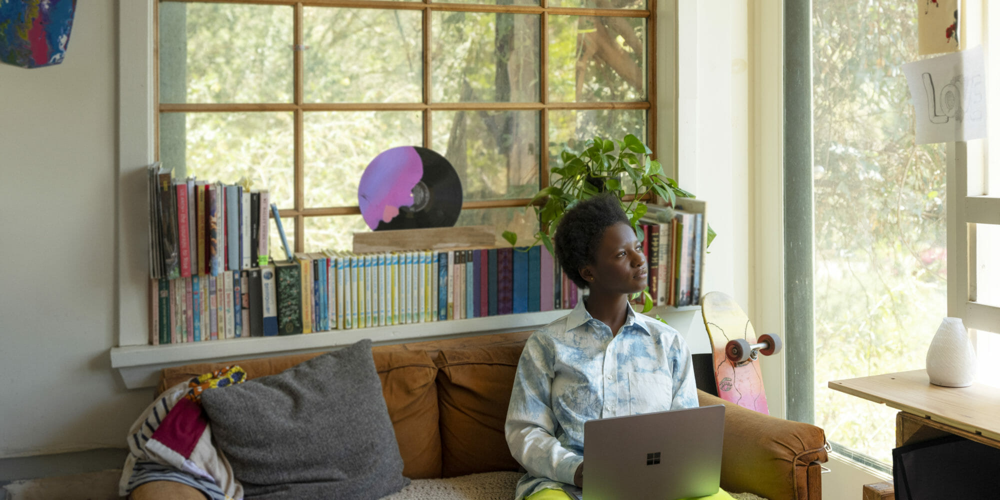 Adult female inside sitting on couch using Surface laptop