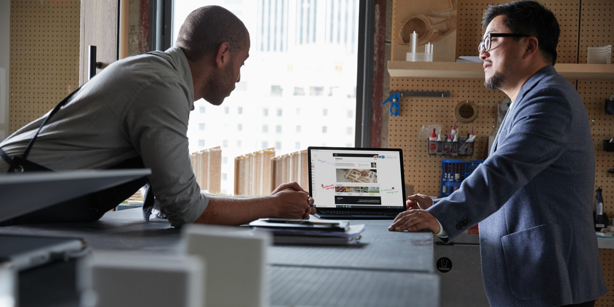 Two adult males looking together on a platinum Microsoft Surface Laptop