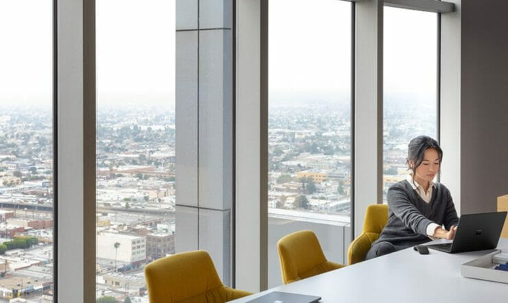woman behind desk with skyline in background