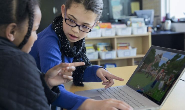 2 young girls playing Minecraft in front of a laptop