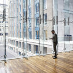 man in front of glass building