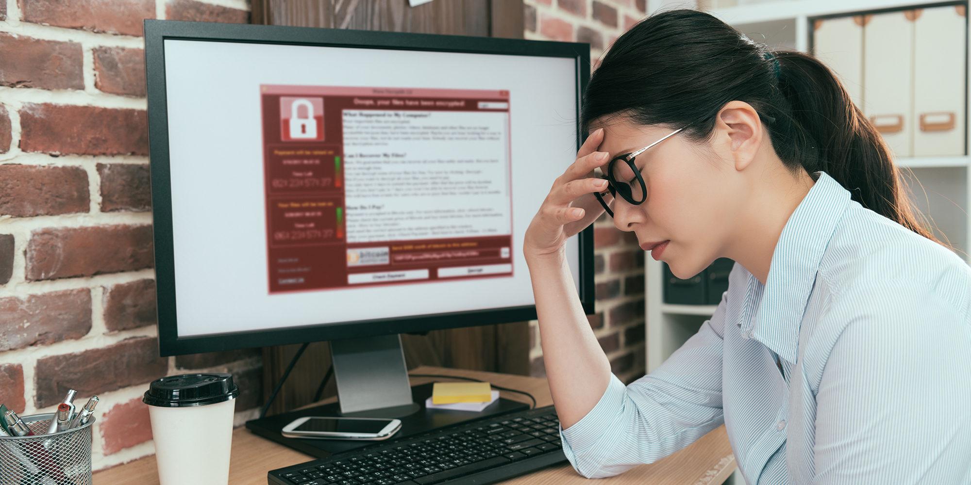 Vrouw die met de handen in de haren zit en merkt dat haar computer gehackt is.