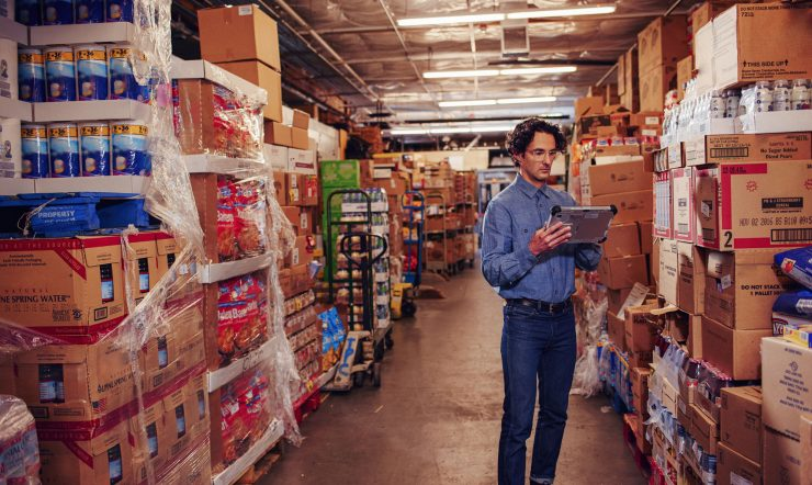 Man inside a warehouse looking at a tablet