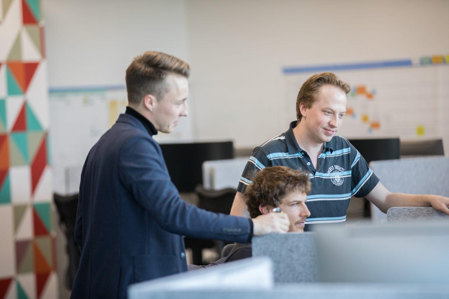 Three men crowded around a computer