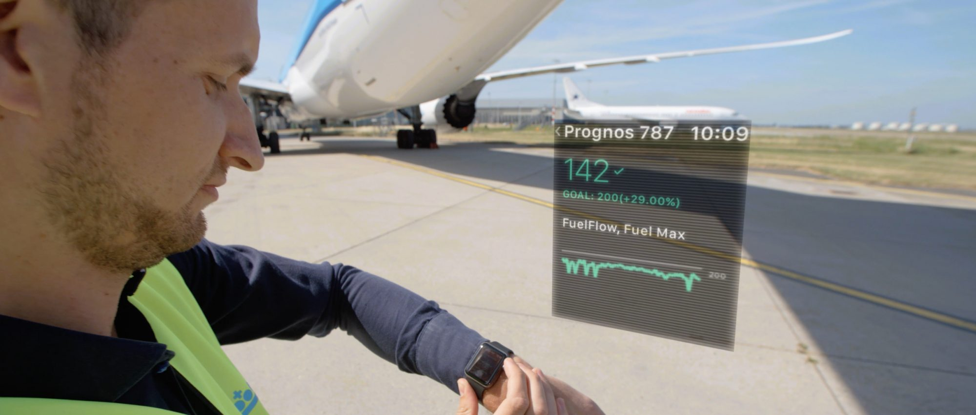 Guy standing next to plane looking at Smartwatch to check reporting.