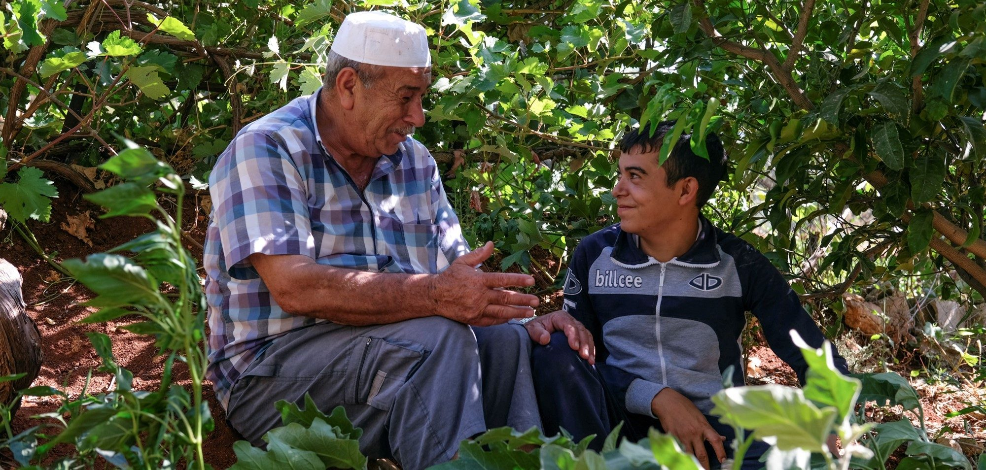 An older man and a younger boy smiling, surrounded by trees
