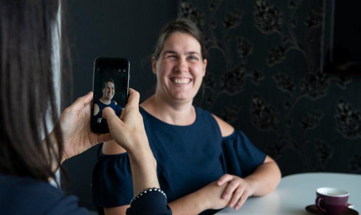 Katrien neemt een foto met een smartphone van een glimlachende Monique