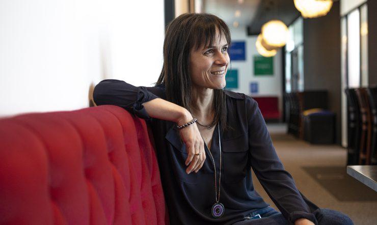 Katrien De Graeve, installée dans un fauteuil, regarde à sa gauche tout en souriant