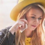 Woman with yellow hat calling