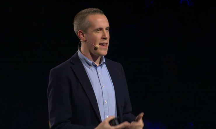 Peter Maynard staat op een podium en geeft een presentatie.