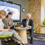Un groupe de trois employés de bureau, deux femmes et un homme, en pleine réflexion dans un bureau au cadre informel. Les deux femmes utilisent leurs ordinateurs portables, l'homme est quant à lui en train d'écrire. Un grand écran est visible en arrière-plan.
