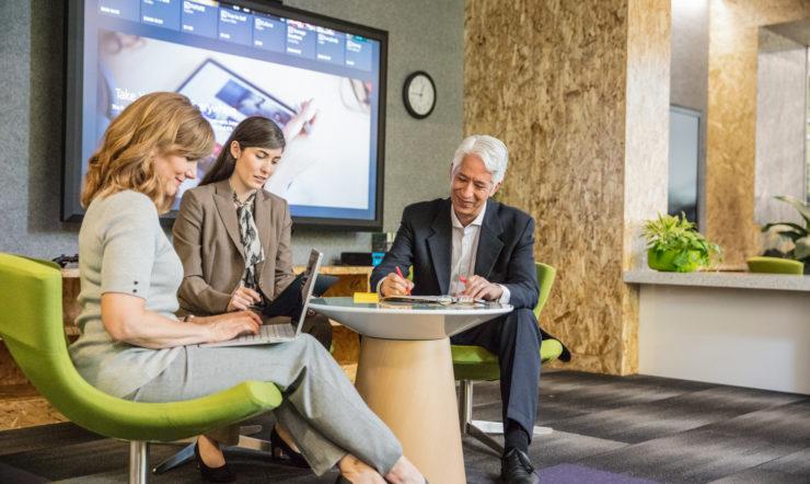 Grupo de duas mulheres e um homem a trabalhar no escritório enquanto debatem num ambiente de escritório informal. As duas mulheres utilizam portáteis enquanto o homem escreve. Grande ecrã apresentado em segundo plano.
