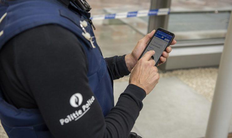 Politieagent die een smartphone in de hand heeft.