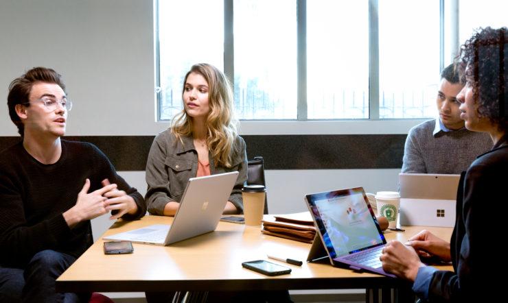 Pessoas em redor de uma mesa em reunião