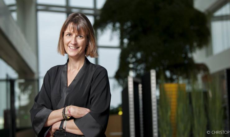 Valérie Pierre, COO Microsoft Belux poseert al lachend in de ontmoetingsruimte van het nieuwe kantoor van Microsoft België.