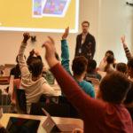 Een groep kinderen die een vinger omhoog steken om antwoord te geven aan de leraar.