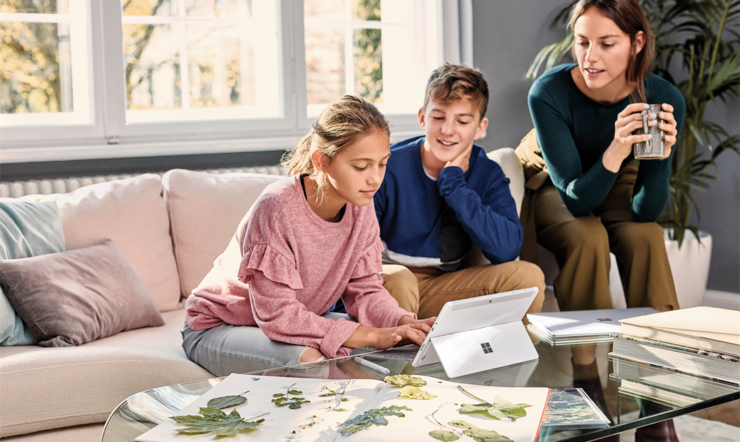 Family, mother and 2 student kids at home working, typing on Surface Go